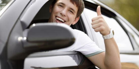 teen driver in good mood with black car selective focus on eyes