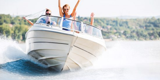 Group of young people with raised hands enjoying in a speedboat ride.
